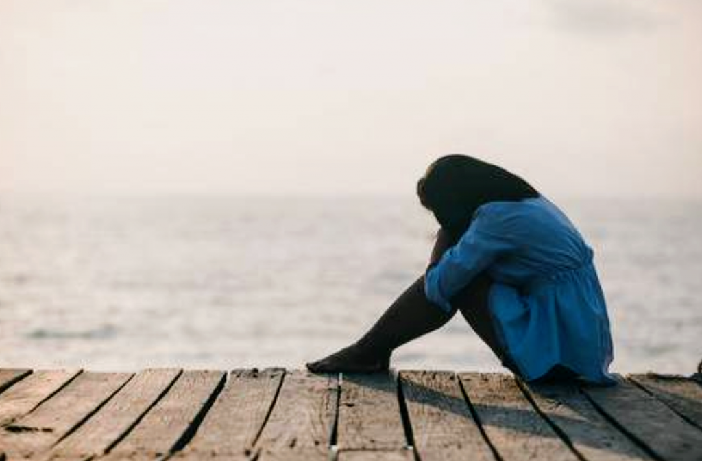 woman with face in knees on dock over looking the water